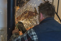 A craftsman grinds to a grinding machine from a weld.