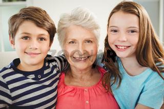 Grandmother and grandchildren sitting together on sofa