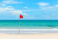 Red flag on tropical beach