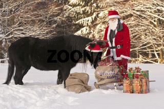 Weihnachtsmann mit Pony im Schnee