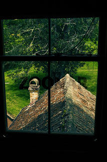 View through the upstairs window over a tiled roof in Huia Lodge