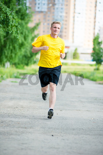 Sporty man jogging in city street park. Outdoor fitness.