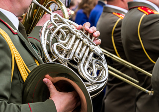military musicians playing french horns on parade