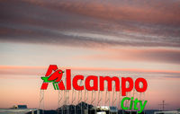 Alicante, Spain- January 12, 2016: Sunset over Alcampo city signboard in Alicante. Alcampo (Auchan) is a French global retail group, had 639 hypermarkets and 2,412 supermarkets around the world. Spain
