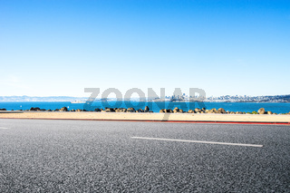 empty asphalt road near  sea with cityscape and skyline of san francisco in blue sky