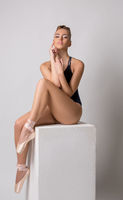 Sensual ballet dancer posing sitting on cube