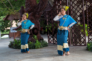 Thai women in traditional dresses dance outside of Sanctuary of Truth Pattaya Thailand