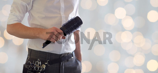 close up of male stylist with brush at salon