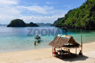 Bald Man pulling wooden traditional filipino boat while two women rest in bamboo hut at white sand beach