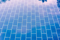 Blue tiled floor of a pool under clear water