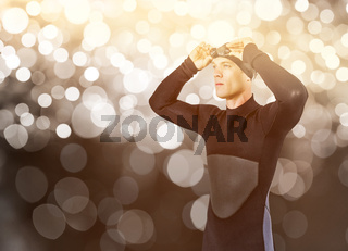 Composite image of swimmer in wetsuit wearing swimming goggles