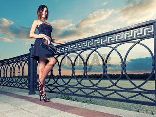 Full Length Portrait of Beautiful Young Woman near Ornate Metal Fence.