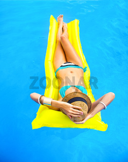 Young pretty woman with perfect tanned body lying on yellow air mattress