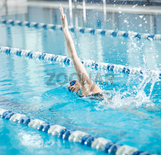 Young girl in goggles swimming front crawl stroke style