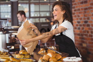 Smiling waitress giving paper bag to customer