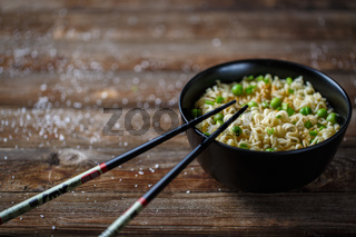 Bowl of noodles with fresh peas and chopped onion.