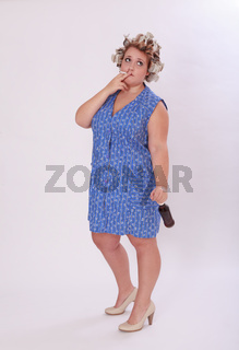 Mollige Frau mit Lockenwickler im Haar die eine Zi