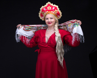 Girl standing in Russian traditional costume. Woman is wearing sarafan and kokoshnik.