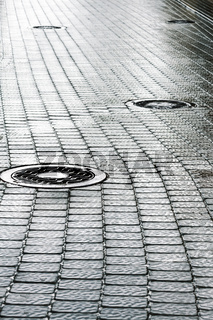 sewer manhole on wet cobblestone street