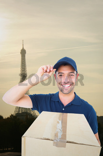 Composite image of happy delivery man wearing cap while holding cardboard box