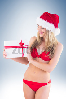 Festive fit blonde in red bikini showing gift