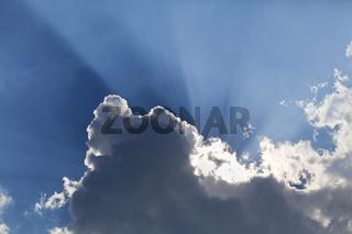 Sun rays through a cloud on a summer day