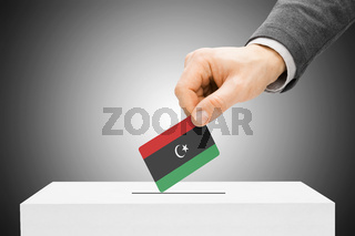 Voting concept - Male inserting flag into ballot box - Libya