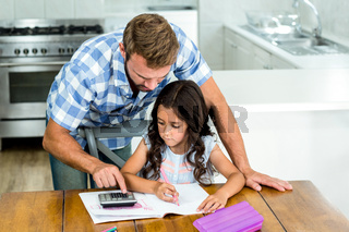 Father assisting daughter in using calculator