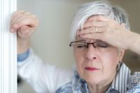 An elderly lady with a headache holds his hand to his forehead.