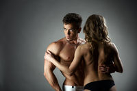 Studio photo of bodybuilder hugs topless model
