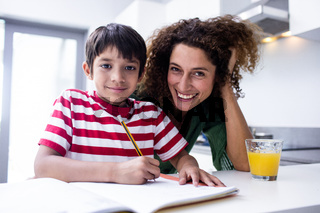 Happy mother helping son with homework