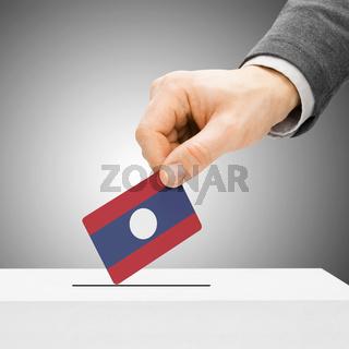 Voting concept - Male inserting flag into ballot box - Laos