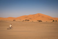 Man riding on a bike in Hassilabied, desert village in Morocco.