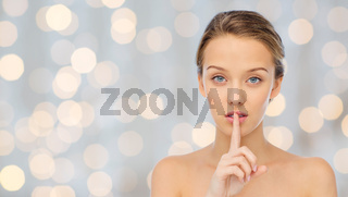 beautiful young woman holding finger on lips