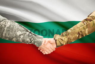 Soldiers shaking hands with flag on background - Bulgaria