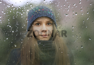 Young girl looking through a window with raindrops