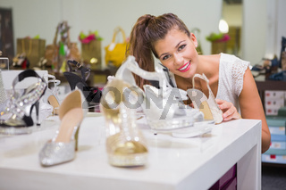 Portrait of smiling woman standing behind shoes