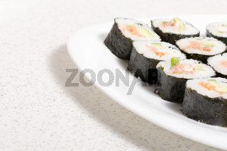 Homemade sushi in a white plate with wasabi and ginger
