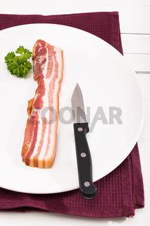 Eine Scheibe Bauchfleisch auf einem weißen Teller