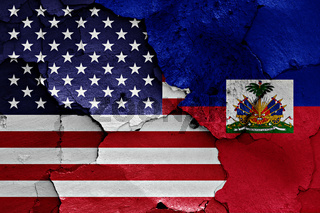 flags of USA and Haiti painted on cracked wall