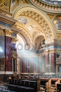 Inside view of St. Stephen's Basilica in Budapest lightened by dramatic sunshine.
