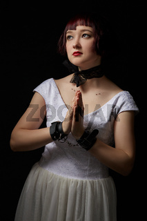 BDSM. Beautiful girl with hands in prayer pose