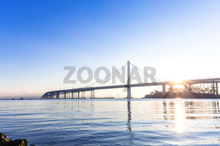 tranquil water and gold gate bridge at sunrise