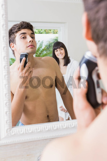 Young man in mirror shaving with electric shaver