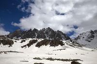 High sunlit rocks, snowy plateau and cloudy sky