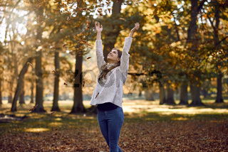 Joyful young woman throwing autumn leaves