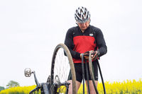 a man repairing a Bicycle in a field, a puncture of a Bicycle camera on the way