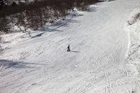 Skier downhill on snowy ski slope at sun winter day