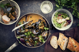 Traditional French blue mussel in bouillabaisse with lettuce and baguette as top view in a casserole