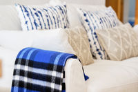 Living room interior with fabric material white colour sofa blue beige elements cushions and plaid close up image no people, modern cozy flat